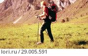 Купить «Hiking man walking on green mountain meadow with backpack. Summer sport and recreation concept.», видеоролик № 29005591, снято 17 апреля 2018 г. (c) Александр Маркин / Фотобанк Лори