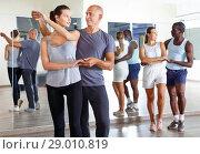 Купить «Young smiling people practicing passionate samba in dance class», фото № 29010819, снято 30 июля 2018 г. (c) Яков Филимонов / Фотобанк Лори
