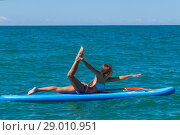 Woman relaxing on a SUP boarding in the sea. Paddle Board Yoga. Healthy lifestyle in harmony with nature. Стоковое фото, фотограф Константин Сиятский / Фотобанк Лори