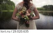 Bride In A Boho Wedding Dress Holding A Bouquet. Стоковое видео, видеограф Pavel Biryukov / Фотобанк Лори
