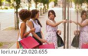 Купить «women with shopping bags looking at shop window», видеоролик № 29020655, снято 22 августа 2018 г. (c) Syda Productions / Фотобанк Лори