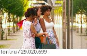 Купить «women with shopping bags looking at shop window», видеоролик № 29020699, снято 15 августа 2018 г. (c) Syda Productions / Фотобанк Лори