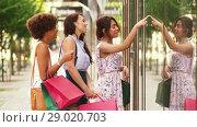 Купить «women with shopping bags looking at shop window», видеоролик № 29020703, снято 15 августа 2018 г. (c) Syda Productions / Фотобанк Лори