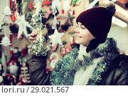 Купить «girl choosing Christmas decoration at market», фото № 29021567, снято 12 декабря 2016 г. (c) Яков Филимонов / Фотобанк Лори
