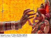 Купить «Close-up of a brides hand applying tilak to ganesh idol», фото № 29029851, снято 5 февраля 2014 г. (c) easy Fotostock / Фотобанк Лори