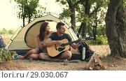 Купить «Young couple playing on guitar in the forest», видеоролик № 29030067, снято 30 августа 2018 г. (c) Илья Шаматура / Фотобанк Лори