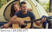 Купить «Man playing guitar for his girlfriend sitting at the camping tent», видеоролик № 29030071, снято 30 августа 2018 г. (c) Илья Шаматура / Фотобанк Лори