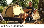 Купить «Backpacker with guitar at forest», видеоролик № 29030075, снято 30 августа 2018 г. (c) Илья Шаматура / Фотобанк Лори