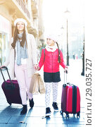 Купить «tourists girl and woman walking with baggage», фото № 29035727, снято 19 ноября 2017 г. (c) Яков Филимонов / Фотобанк Лори