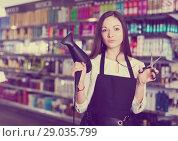 Купить «Woman hairstylist holding blow dryer and hair cutters in cosmetics salon», фото № 29035799, снято 31 марта 2018 г. (c) Яков Филимонов / Фотобанк Лори