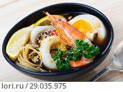 Купить «Spicy pan-Asian soup with squid, shrimp, egg noodles with sesame», фото № 29035975, снято 21 октября 2018 г. (c) Яков Филимонов / Фотобанк Лори