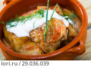 Купить «Tasty cabbage rolls in leaves of cabbage in clay pot with sour cream», фото № 29036039, снято 21 сентября 2018 г. (c) Яков Филимонов / Фотобанк Лори