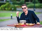 Купить «Young man eating take away noodles on the street», фото № 29036707, снято 20 июля 2018 г. (c) Дмитрий Травников / Фотобанк Лори