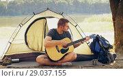 Купить «Traveler play guitar on nature», видеоролик № 29037155, снято 31 августа 2018 г. (c) Илья Шаматура / Фотобанк Лори