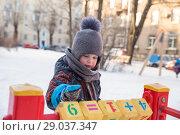 Купить «Мальчик 4 года зимой на детской площадке играет кубиками с цифрами», фото № 29037347, снято 21 марта 2018 г. (c) Юлия Бабкина / Фотобанк Лори