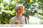 Купить «senior woman walks along park and drinks coffee», видеоролик № 29037943, снято 21 августа 2018 г. (c) Syda Productions / Фотобанк Лори