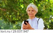 Купить «senior woman photographing at summer park», видеоролик № 29037947, снято 21 августа 2018 г. (c) Syda Productions / Фотобанк Лори