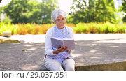 Купить «senior woman reading book at summer park», видеоролик № 29037951, снято 21 августа 2018 г. (c) Syda Productions / Фотобанк Лори
