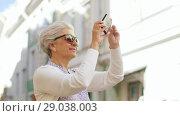 Купить «senior woman photographing by smartphone in city», видеоролик № 29038003, снято 21 августа 2018 г. (c) Syda Productions / Фотобанк Лори