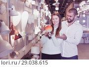 Купить «Smiling family holding bedside lamp in furniture shop», фото № 29038615, снято 29 января 2018 г. (c) Яков Филимонов / Фотобанк Лори