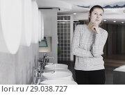 Купить «Smiling female buyer choosing ceramic washbasin in store», фото № 29038727, снято 2 февраля 2018 г. (c) Яков Филимонов / Фотобанк Лори
