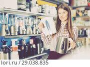 Купить «Young attractive woman choosing kettle in household appliances store», фото № 29038835, снято 12 декабря 2017 г. (c) Яков Филимонов / Фотобанк Лори