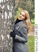 Купить «Девушка в осеннем пальто около дерева», фото № 29041307, снято 5 октября 2013 г. (c) Александр Гаценко / Фотобанк Лори