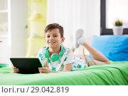 Купить «smiling boy with tablet pc computer at home», фото № 29042819, снято 19 апреля 2018 г. (c) Syda Productions / Фотобанк Лори