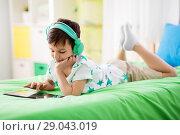 Купить «smiling boy with tablet pc and headphones at home», фото № 29043019, снято 19 апреля 2018 г. (c) Syda Productions / Фотобанк Лори
