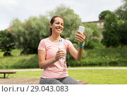 Купить «woman with smartphone, water and fitness tracker», фото № 29043083, снято 15 июня 2018 г. (c) Syda Productions / Фотобанк Лори