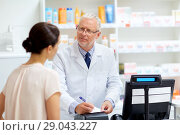 Купить «senior apothecary with prescription at pharmacy», фото № 29043227, снято 27 июня 2015 г. (c) Syda Productions / Фотобанк Лори