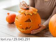 Купить «close up of woman with halloween pumpkin at home», фото № 29043291, снято 15 сентября 2017 г. (c) Syda Productions / Фотобанк Лори