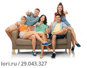 Купить «friends sitting on sofa and showing thumbs», фото № 29043327, снято 30 июня 2018 г. (c) Syda Productions / Фотобанк Лори