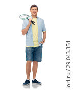 Купить «smiling young man with badminton rackets», фото № 29043351, снято 30 июня 2018 г. (c) Syda Productions / Фотобанк Лори