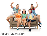 Купить «friends or football fans with soccer ball on sofa», фото № 29043591, снято 30 июня 2018 г. (c) Syda Productions / Фотобанк Лори