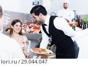 Купить «waiter bringing ordered seafood dishes to smiling couple», фото № 29044047, снято 26 января 2018 г. (c) Яков Филимонов / Фотобанк Лори