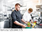 Купить «chef and cook cooking food at restaurant kitchen», фото № 29044175, снято 2 апреля 2017 г. (c) Syda Productions / Фотобанк Лори