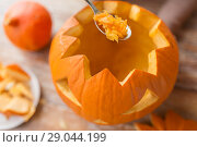 Купить «close up of spoon carving halloween pumpkin», фото № 29044199, снято 15 сентября 2017 г. (c) Syda Productions / Фотобанк Лори