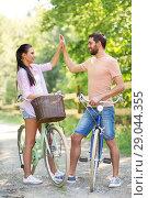 Купить «couple with bicycles making high five in summer», фото № 29044355, снято 15 июля 2018 г. (c) Syda Productions / Фотобанк Лори