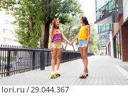 Купить «teenage girls riding skateboards in city», фото № 29044367, снято 19 июля 2018 г. (c) Syda Productions / Фотобанк Лори