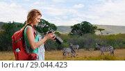 Купить «woman with backpack and camera over savannah», фото № 29044423, снято 25 июля 2015 г. (c) Syda Productions / Фотобанк Лори