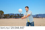Купить «smiling young man playing volleyball», фото № 29044447, снято 30 июня 2018 г. (c) Syda Productions / Фотобанк Лори