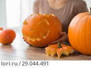 Купить «close up of woman with halloween pumpkin at home», фото № 29044491, снято 15 сентября 2017 г. (c) Syda Productions / Фотобанк Лори