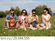 Купить «smiling friends with smartphones sitting on grass», фото № 29044555, снято 7 июля 2018 г. (c) Syda Productions / Фотобанк Лори