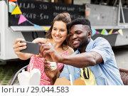 Купить «mixed race couple taking selfie at food truck», фото № 29044583, снято 1 августа 2017 г. (c) Syda Productions / Фотобанк Лори