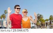 Купить «couple in sunglasses hugging and waving hands», фото № 29044675, снято 30 июня 2018 г. (c) Syda Productions / Фотобанк Лори