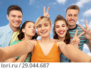 Купить «happy friends taking selfie and showing peace», фото № 29044687, снято 30 июня 2018 г. (c) Syda Productions / Фотобанк Лори
