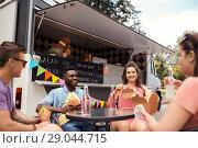 Купить «happy friends with drinks eating at food truck», фото № 29044715, снято 1 августа 2017 г. (c) Syda Productions / Фотобанк Лори