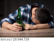 Купить «drunk man with beer bottles on table at night», фото № 29044739, снято 24 ноября 2017 г. (c) Syda Productions / Фотобанк Лори