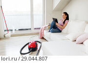 Купить «woman with tablet pc and vacuum cleaner at home», фото № 29044807, снято 29 апреля 2018 г. (c) Syda Productions / Фотобанк Лори
